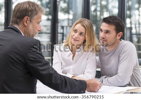 young couple meeting real estate agent for future house - stock photo