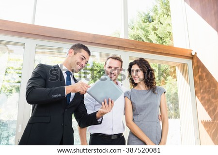 Young couple meeting real-estate showing a house project on a digital tablet - stock photo