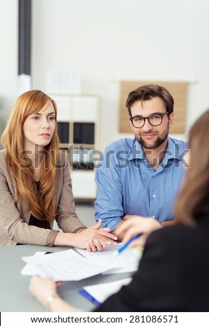 Young couple meeting with a broker or agent sitting at her desk in the office listening to te presentation with attentive expressions - stock photo