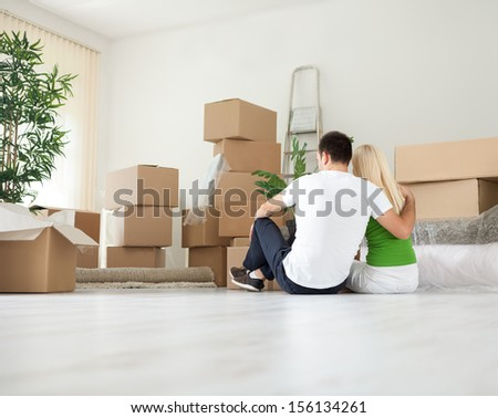 Young couple moving house resting in room full of boxes  - stock photo