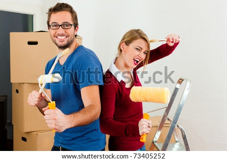 Young couple moving in a home or apartment, they are painting and doing renovation work - stock photo