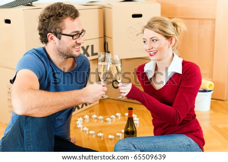 Young couple moving in a home or apartment, they are sitting on the wood floor drinking champagne having a break from renovation - stock photo