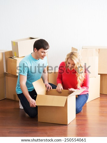 Young couple moving in a new home. Man and woman unboxing fragile stuff. Positive emotions.