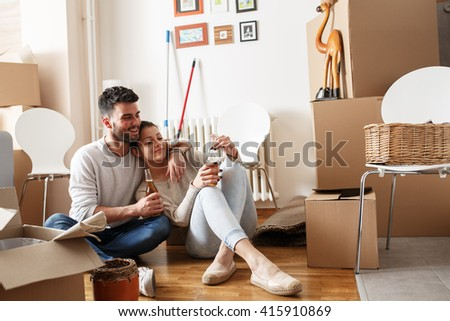 Young couple Moving in new home.Sitting on floor and relaxing after cleaning and unpacking. - stock photo