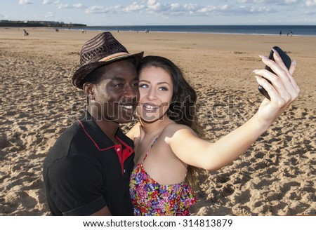 Young couple multicultural taking selfie laughing  in love  on beach having fun - stock photo