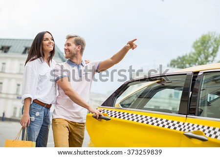 Young couple near a yellow taxi - stock photo
