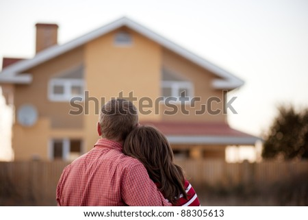 young couple near his house - stock photo