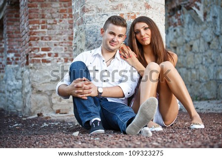 Young couple near ruined brick wall - stock photo