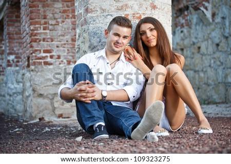 Young couple near ruined brick wall - stock photo