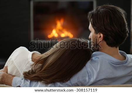 young couple next to the fireplace - stock photo