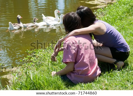 Young couple observing of geese in lake - stock photo