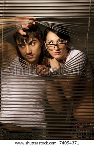 Young Couple observing through a jalousie - stock photo