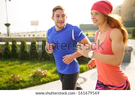 Young couple of athletes running on the empty street in the morning. The man is looking at his partner. Everyone is smiling. - stock photo