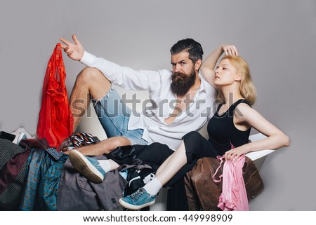 young couple of blonde pretty girl and handsome bearded man with long beard on bathtub with many colorful clothes on grey background