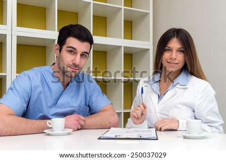 Young couple of doctor and nurse having a break and relaxing with a cup of coffee in medical center. - stock photo
