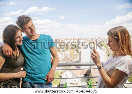 Young Couple Of Friends On A Balcony Taking A Photo - stock photo
