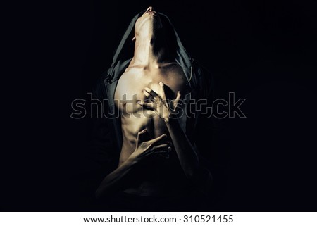 Young couple of guy with sexy strong muscular body in leather jacket with hood looking up and girl embracing with hands standing on studio black background, horizontal picture - stock photo