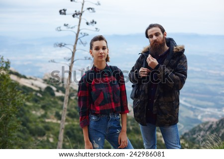 Young couple of hikers with backpacks standing on mountain hill with amazing view on background - stock photo