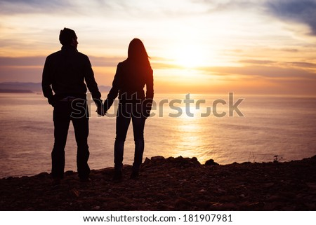 Young couple of lovers holding hands towards the sea at sunset. Man and woman in love looking the sun and ocean together. - stock photo