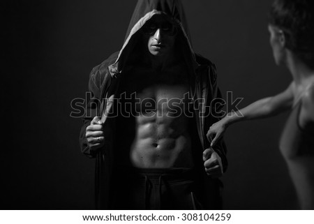 Young couple of man with sexy strong muscular beautiful body in leather jacket with hood and sunglasses and undressed woman standing in studio black and white, horizontal picture - stock photo