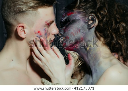 Young couple of muscular handsome man and sexy woman with paited face and bare body