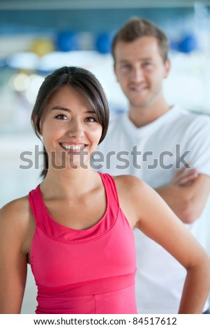 Young couple of people smiling at the gym - stock photo