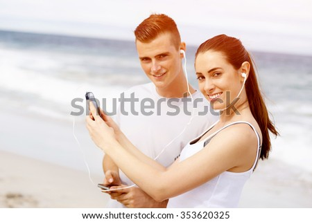 Young couple of runners with mobile smart phone outdoors on beach - stock photo