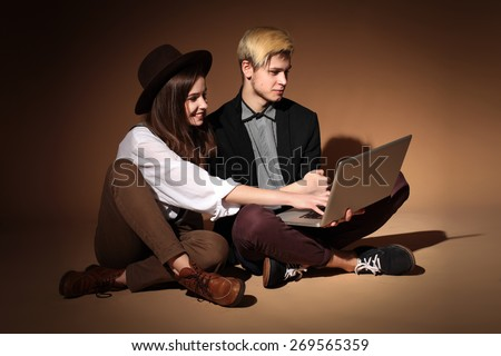 Young couple of students with laptop, teenage couple sitting at a laptop, learning, study - stock photo