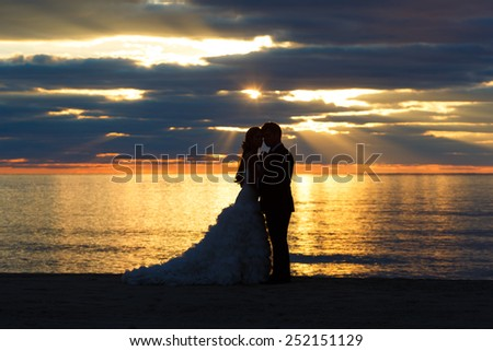 Young couple of sweethearts hugging along the seacoast - stock photo