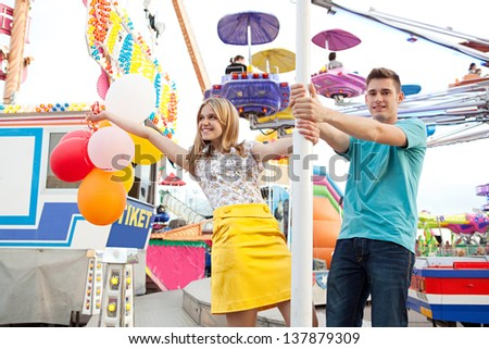 Young couple of teenagers visiting a fun fair ground with rides and lights around them, holding balloons and being playful during a sunny day. - stock photo