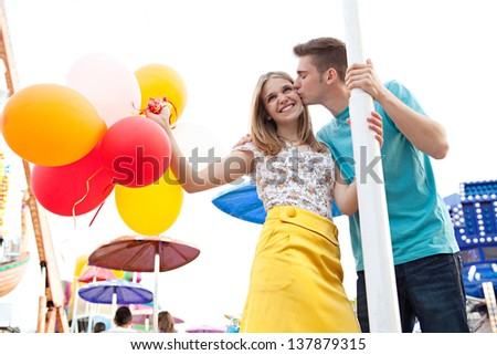 Young couple of teenagers visiting a fun fair ground with rides and lights around them, holding balloons, being joyful and kissing during a sunny day. - stock photo