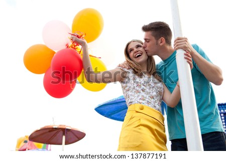 Young couple of teenagers visiting a fun fair ground with rides around them, holding balloons, being joyful and kissing during a sunny day. - stock photo