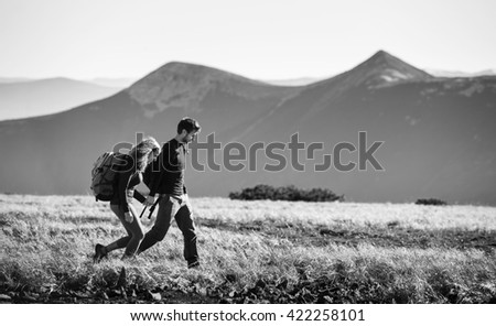 Young couple of tourists enjoying their trip in the mountains. Side view with big beautiful mountains on the background. Travelers holding hands. black and white - stock photo
