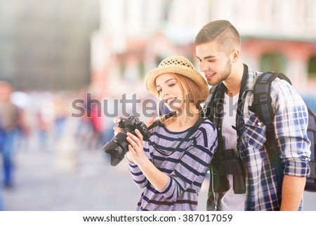 Young couple of travelers with camera on the street, outdoors