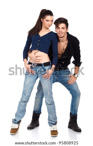Young couple of two attractive happy fashion models wearing jeans looking at camera. Isolated on white background. High resolution studio image