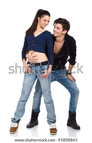 Young couple of two attractive happy fashion models wearing jeans looking at each other. Isolated on white background. High resolution studio image