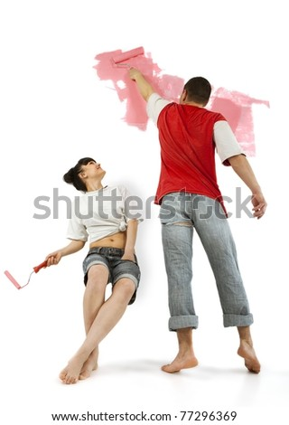 Young couple of workers painting on a wall with roller - stock photo