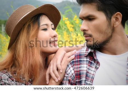 Young couple off work off time during honeymoon vacation with yellow flowers field and mountain behind : Love concept, travel concept