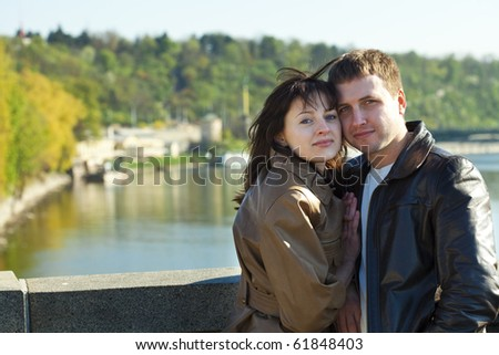 young couple on a bridge on the river - stock photo