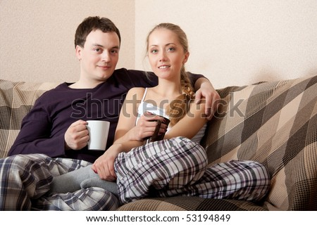 Young couple on a couch, in living room