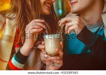 young couple on a date drinking one cup of cappuccino. close up horizontal photo - stock photo