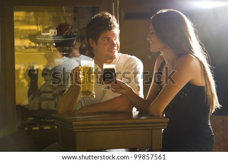 Young couple on a date enjoying their drink in a pub/bar - stock photo