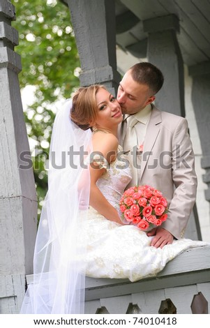 Young couple on a formal wedding photo. The groom kisses bride. - stock photo