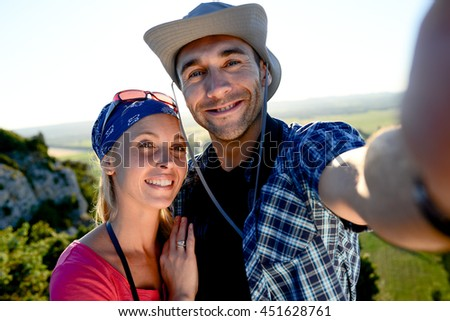 young couple on a hiking adventure trek making selfie with beautiful sunset landscape - stock photo