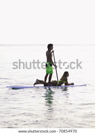 young couple on a paddle board in a hawaii lagoon - stock photo