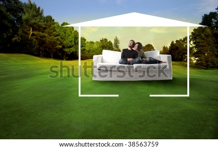 young couple on a sofa in a beautiful natural landscape surrounded by home drawing - stock photo