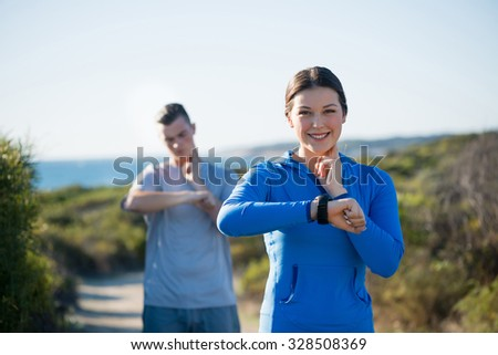 Young couple on beach checking heart rate after run - stock photo