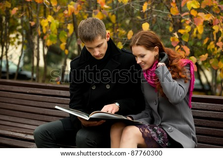 young couple on bench in autumn park and read book