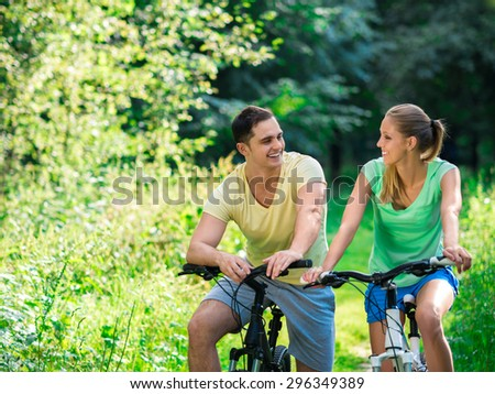 Young couple on bicycles outdoors - stock photo