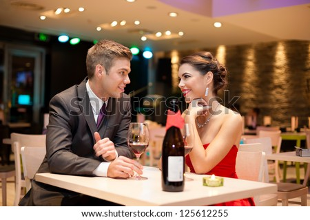 Young couple on first date in romantic restaurant - stock photo